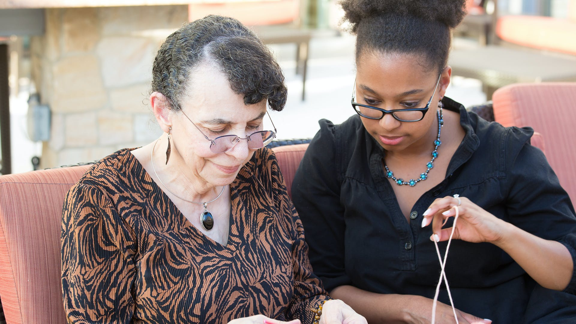 Elderly lady knitting being supported by her carer