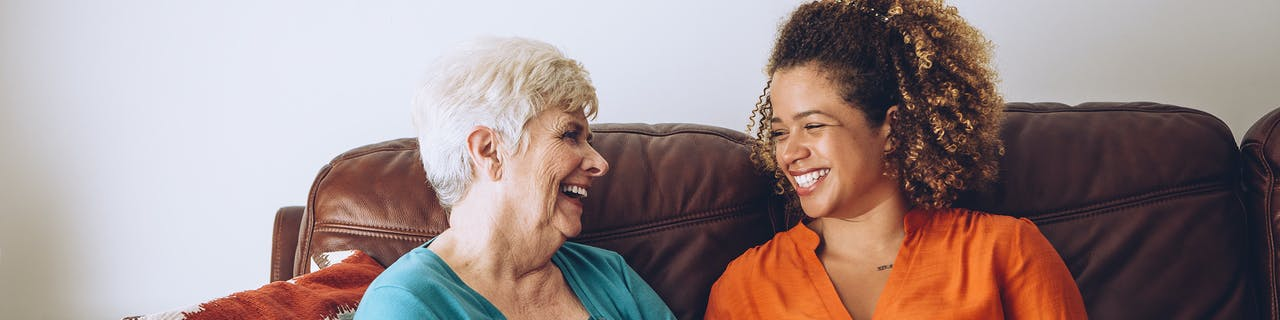 Live-in carer sitting with her elderly client on the sofa with both people smiling